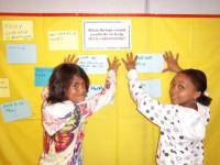 Children with hands on wall