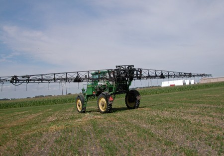 Green HIgh Sprayer with arms out in a field