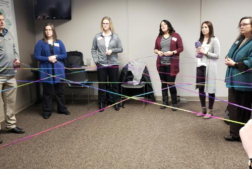 Group networks are illustrated by running yarn between people who know each other on different scales.