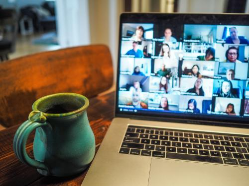 Laptop with virtual meeting on screen and a coffee cup to the left