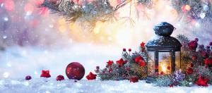 Winter scene with a lantern, pine branches, snow, and ornaments.