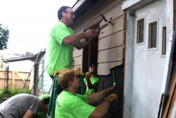 Men repairing the outside of a home.