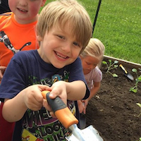 Smiling boy with spade in garden.