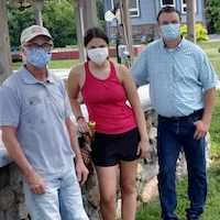 Three people outdoors in masks.