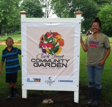 Boy and woman stand next to community garden sign.