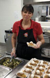 Food service worker serves vegetables and dessert.
