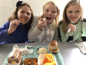 Three girls eat school lunch featuring local food.