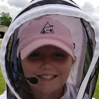 Girl in bee-keeping helmet.