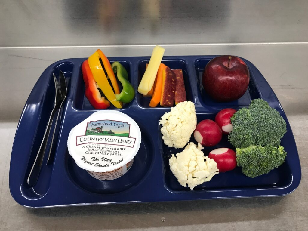 Food tray with fruits, vegetables and cup of yogurt.
