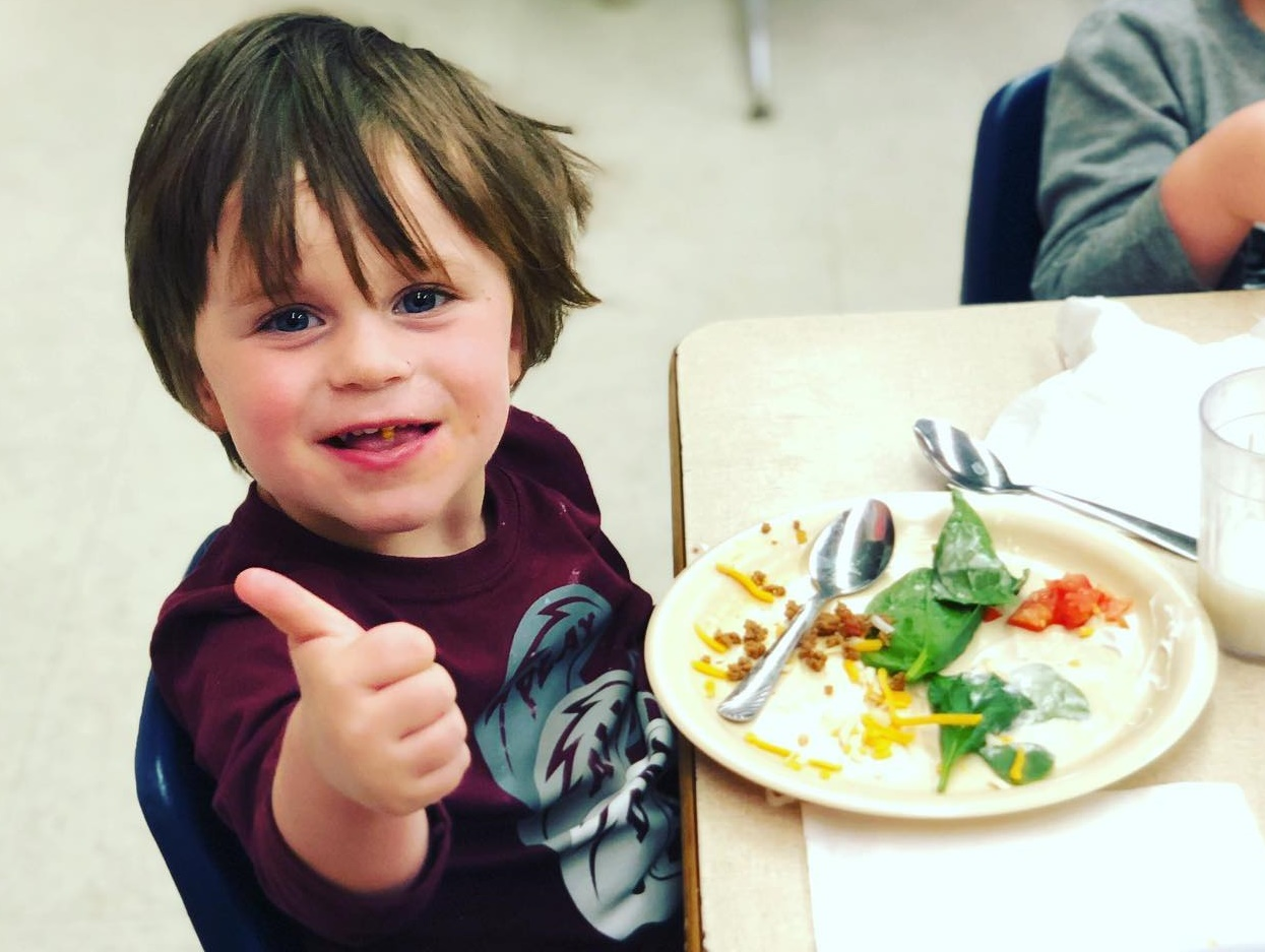 Preschool boy with snack plate gives thumbs up.