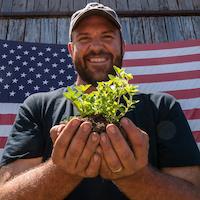 Smiling man holds seedlings.