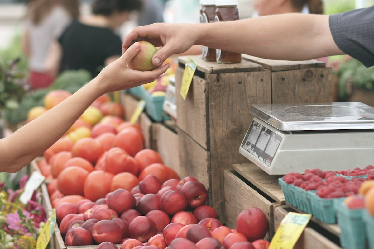 One person hands apple to another over a display of fruit at farmers market.