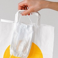 Hand holding shopping bag and face mask.