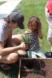 Carissa helping one of the kids plant in their garden.