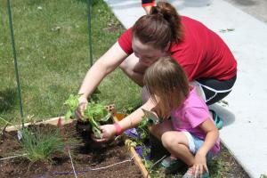 Christel showing one of the kids how to plant in their garden.