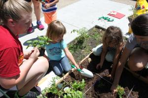 Emily and Carissa helping some kids put plants in the garden