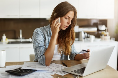 woman using cell phone regarding credit card that she is holding by Wayhome Studio/stock.adobe.com.