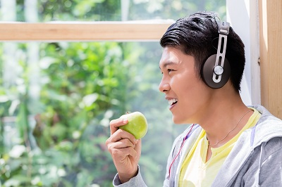 person eating a fresh green apple while listening to stereo headphones indoors by Kzenon/stock.adobe.com.