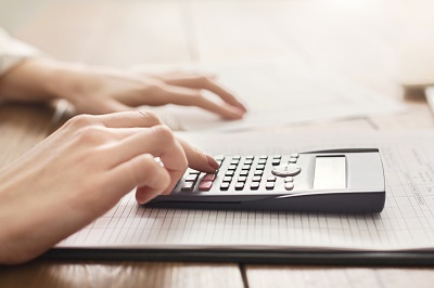 Woman using calculator by Prostock-studio/stock.adobe.com.