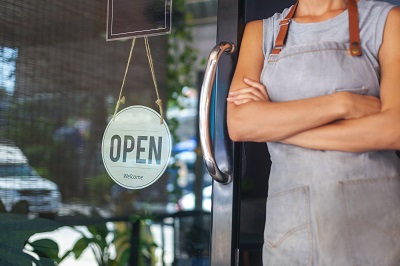 woman in apron at door of small business with open sign by olezzo/stock.adobe.com.