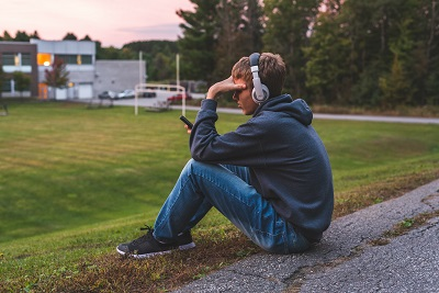 Upset teenager sitting on the ground all alone while listening to some music by Brian/stock.adobe.com.