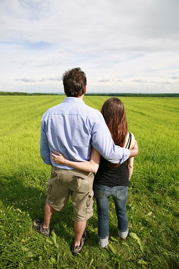 Young couple hugging and overlooking farmland by Pierre/stock.adobe.com.