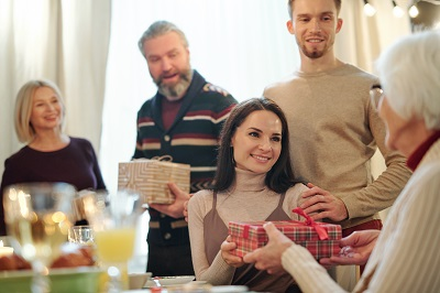 family gives wrapped gift to grandmother by pressmaster/stock.adobe.com.