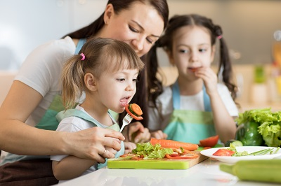 mom with daughters chopping vegetables in home kitchen by Oksana Kuzmina/stock.adobe.com.