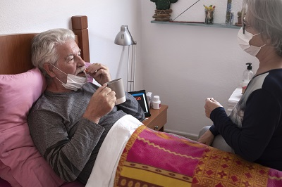 caregiver gives medicine to older adult at home by luciano/stock.adobe.com.