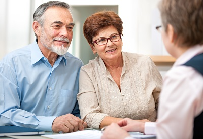 Senior couple discussing finances with consultant by Alexander-Raths/stock.adobe.com.