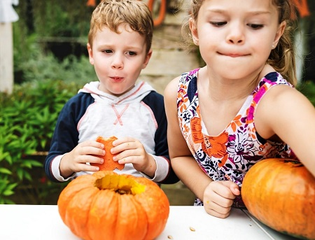 two small children with pumpkins.