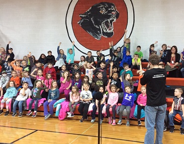 AmeriCorps student teaching an elementary school audience.