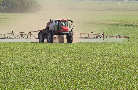 agricultural chemical sprayer moving across a field.