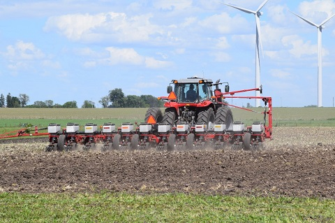 tractor pulling corn planter in field.