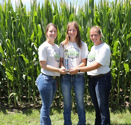 team of three young ladies in front of a field of corn.