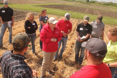 crop scouts listening to extension specialist in field.