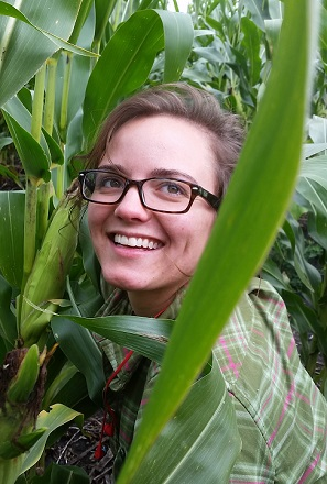 Emily Waring headshot surrounded by tall corn stalks.