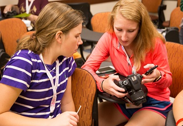 two 4-H'ers looking at images on camera.