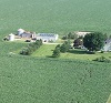 aerial view of farmstead with green fields all around.