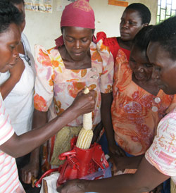 Ugandan women use a corn sheller