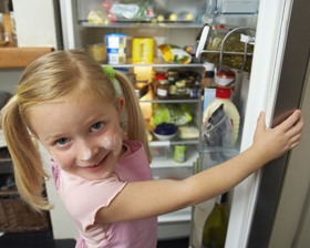 Child standing in front of open refridgerator