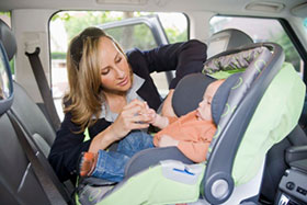 parent placing child in car seat