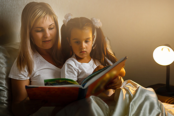 mother and child girl reading a book in bed Angelov/stock.adobe.com