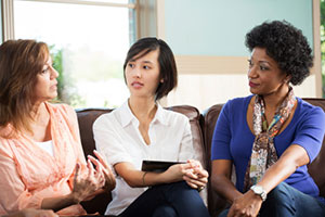 three women of various racial-ethnic backgrounds talk together