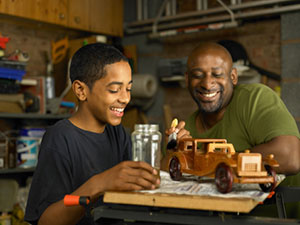 father helps son with woodworking project