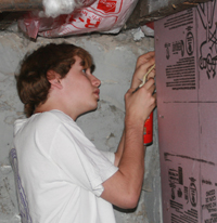 youth installs insulation around basement window