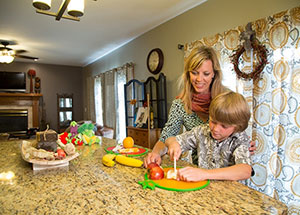 mother watches as son cuts fruit in kitchen