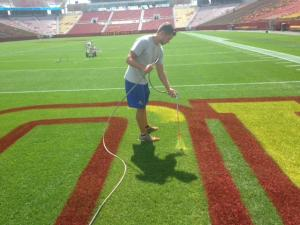 ISU Horticulture students studying turfgrass management help paint the football field.