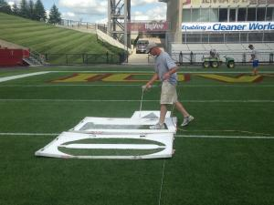 Number stencils are placed every 10 yards and painted white.