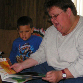 Women reading book to child